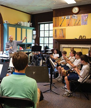 Upper School students in the Advanced Music Composition and Production class observe as their musical compositions are performed  by the fifth grade music ensemble, directed by Harley Givler.