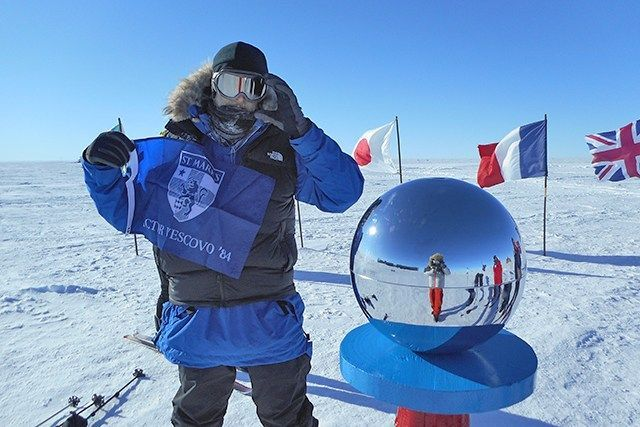 Victor displays his St. Mark's flag at the South Pole.