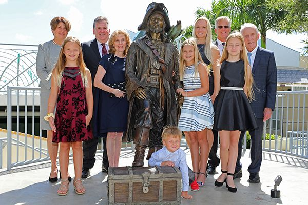 Ansin family members surround the Raider statue in 2018