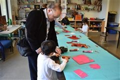 Ardavan Tehrani printmaking with his son in Ms. Bedingfield's art class.