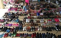 Lindsay with all the shoes she collected for Shoes for Souls!