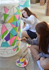 A stained-glass effect takes shape on a white rain barrel.