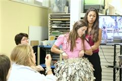 Alice-Anne Augustin helps Mia Iannios '21 model one of her paper skirts.