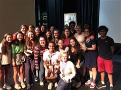 Texas French Symposium students along with French teacher Shelley Stein celebrate onstage with the team's first place trophy.