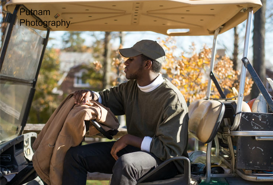 Mike Lazarre '18 poses on a golf cart.