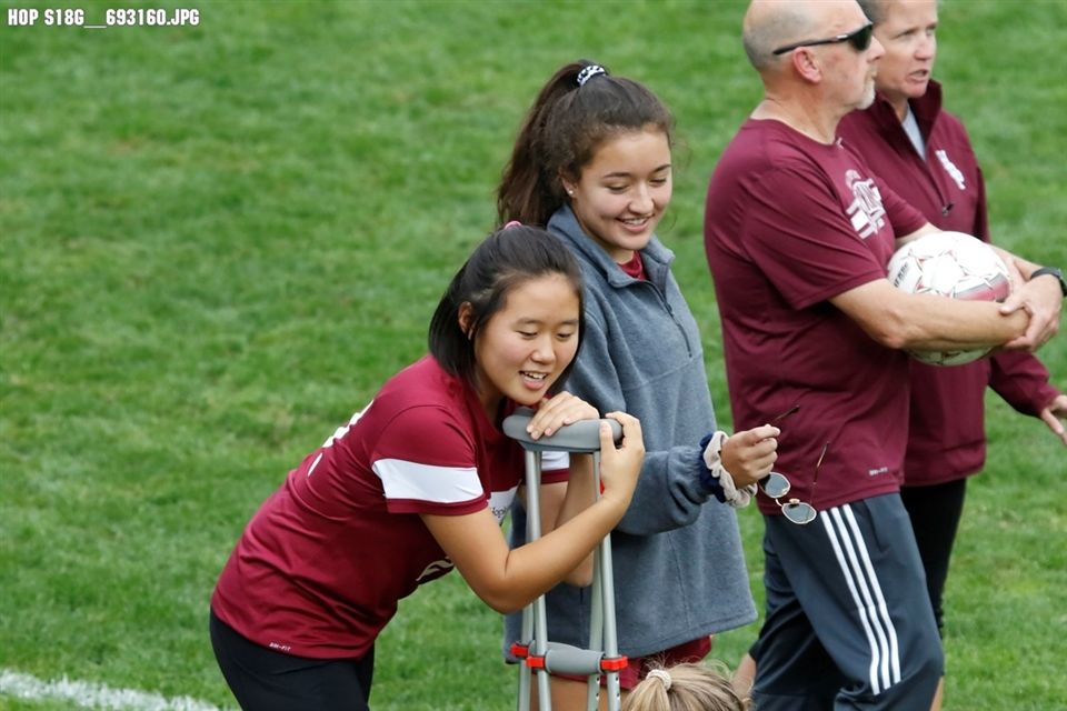 Zoe Kim '20 watches a soccer game with her coaches and teammate Lily Fagan '20.