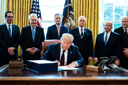 President Trump signs into law the $2.2 trillion CARES Act. Photo by Erin Schaff