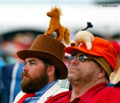 Two men observe the 2016 Kentucky Derby while wearing their Derby-themed hats