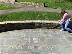"Sophomore Casey Goldberg '20 chalks ""Easter-Wings"" by George Herbert outside of the Kneisel Squash Center."