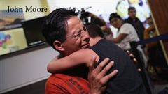 A father and his son embrace after eventually being reunited.