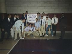"Members of Boys Water Polo pose in front of one of the ""We Think""- themed signs found at this year's Homecoming dance"