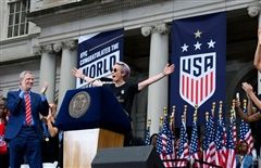 Megan Rapinoe celebrates team USA in front of a large crowd.