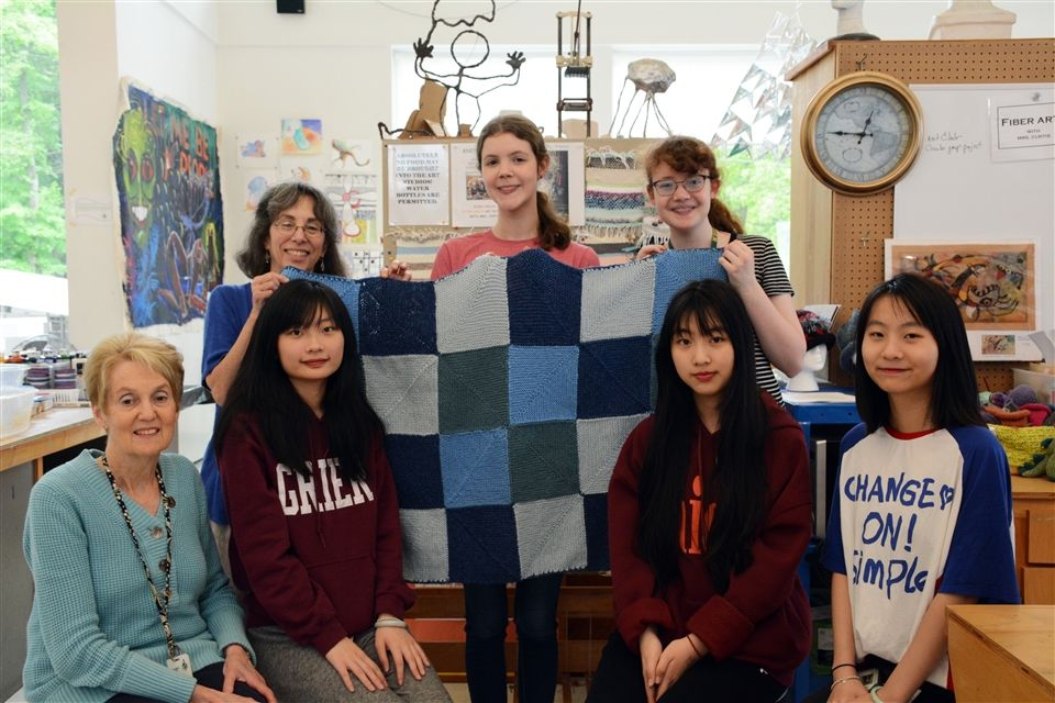 Members of Knitting Club and the completed baby blanket. Heather P. (center) led the effort.