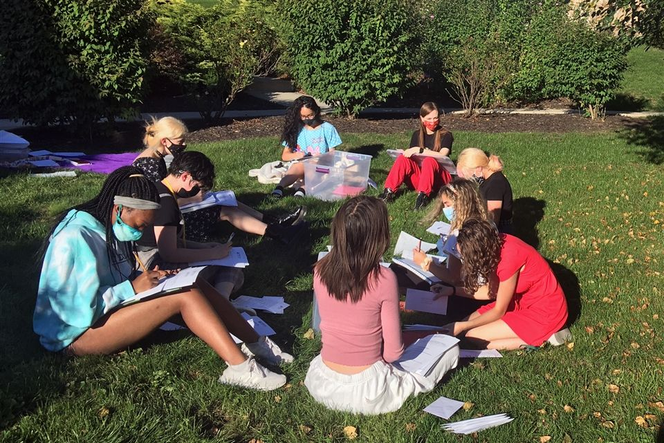 Students enjoying a sunny September afternoon while they write letters to PA voters.