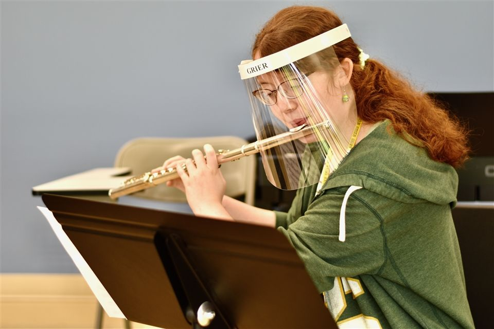 Lizzie P. plays a flute beneath a face shield.
