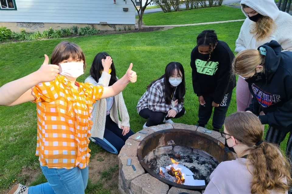 Campbell C. ignites the first fire and her classmates toss their old homework into the firepit a ceremonial burning.