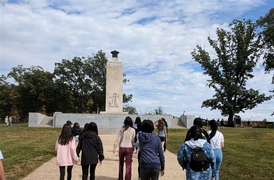 A group of students walk toward the Enduring Peace Monument, erected in 1935 by President Franklin D. Roosevelt.