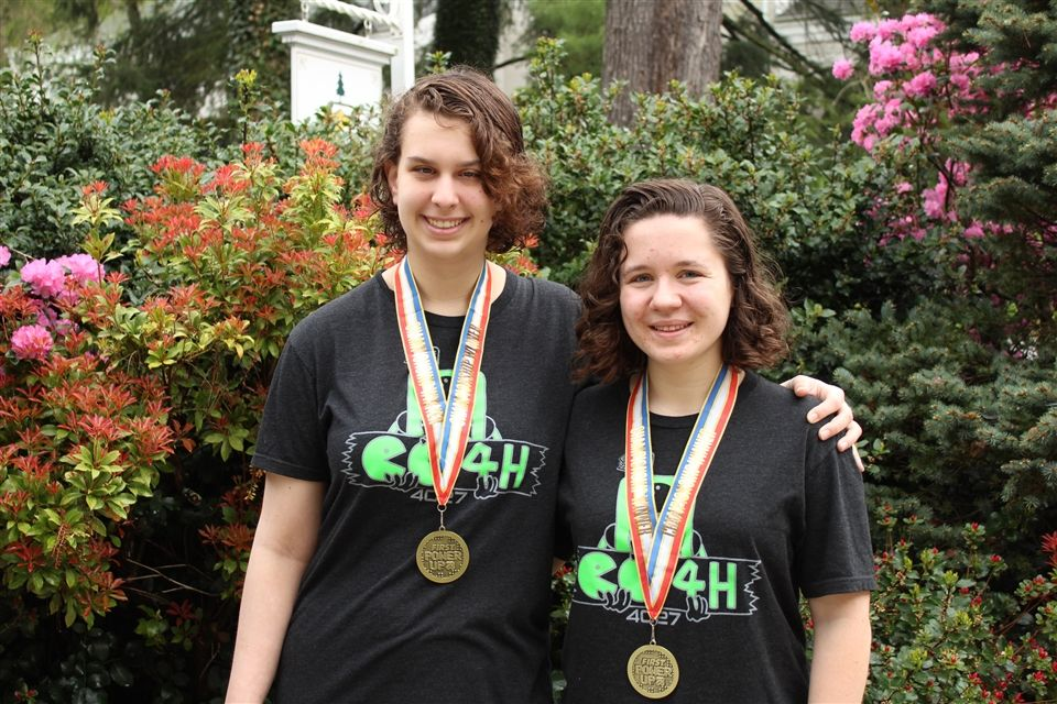 Emily and Mary in their team shirts with medals.