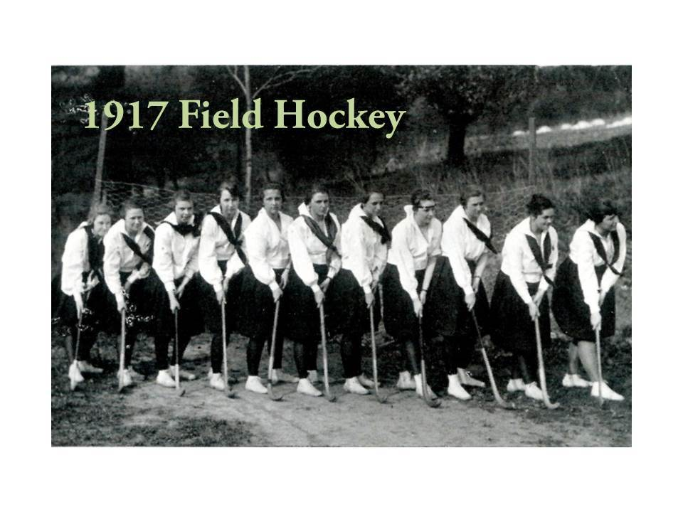 In the 1917 yearbook, a group of Grier girls pose for a Field Hockey team photo. They wear white blouses adorned with a school-girl kerchief, full knee-length skirts, tights, and surprisingly athletic-looking shoes.
