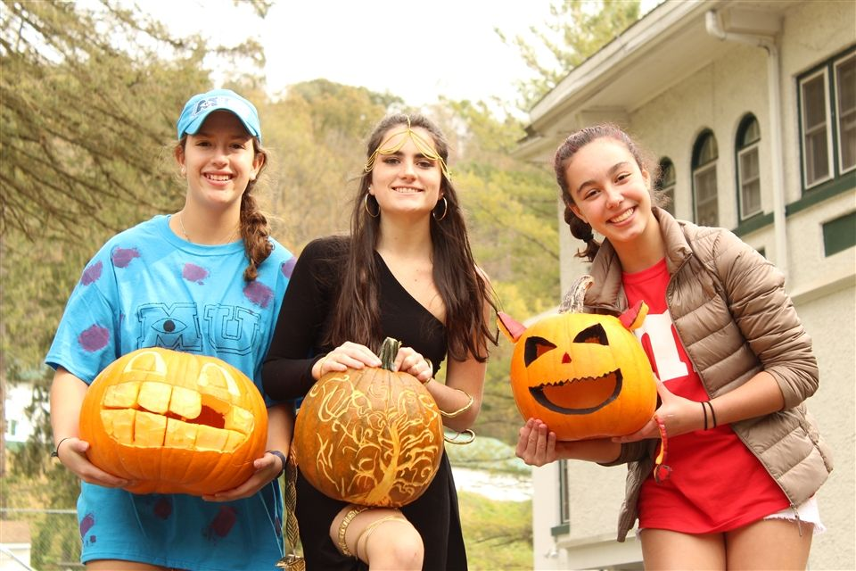 Students in costume hold their finished Jack-o-Lanterns.
