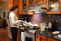 Maria sauteing a crepe in the Maple House kitchen.