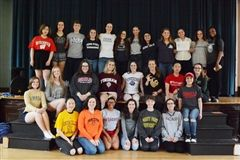 Seniors gather proudly in shirts reflecting their college choices.