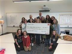 Middle School students accept a $2,000 check from Wells Fargo