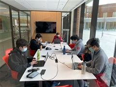 Five male students sitting around a white desk working on the Canadian Computing Competition