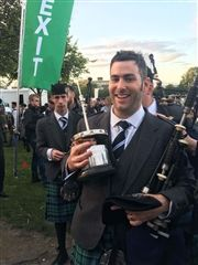 Andrew Douglas '03 holds the World Pipe Band Championship trophy, affectionately known as