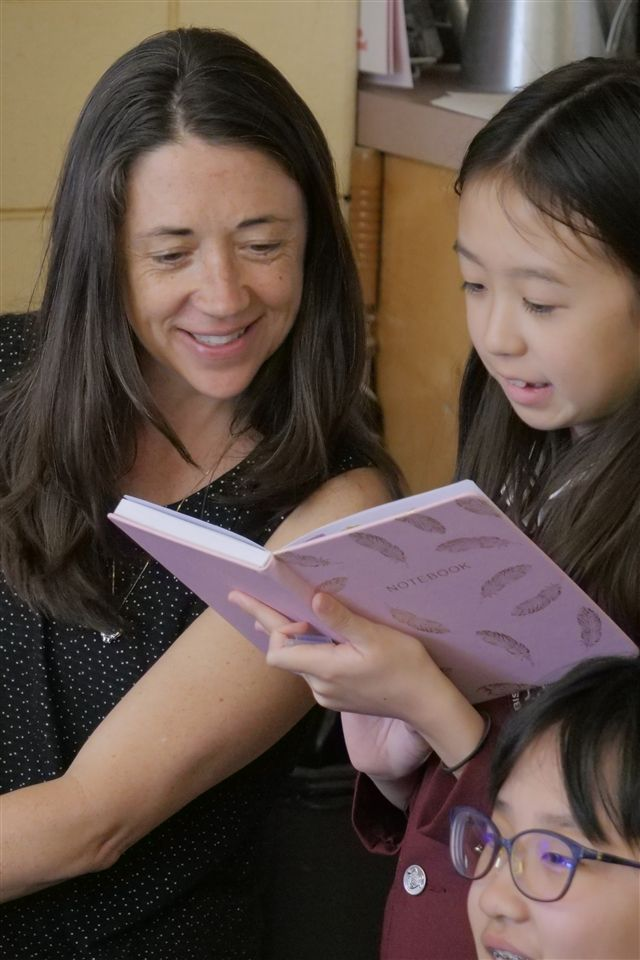 Junior School teacher Kerri Embry reads a book with a young student