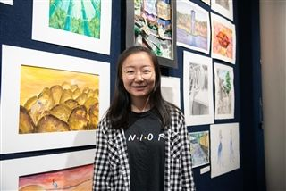 Sherry in front of some of her art at the AP Honors Art show.