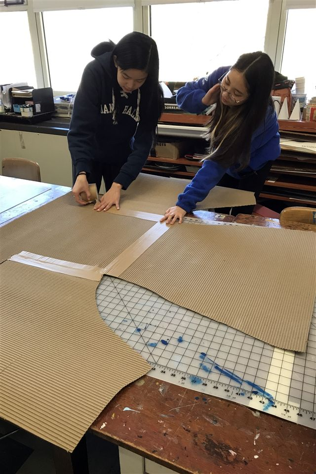 Students constructing large-scale cardboard chair