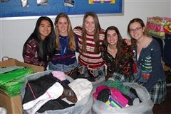 Members of Marian's Spanish Honor Society pack warm clothing, including hats, gloves, scarves, and jackets to deliver to Neinas Elementary School in Detroit.