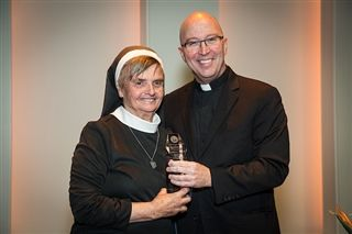 Fr. McGrath presents the Rev. Daniel A. Lord, SJ, Award for Distinguished Service in the Cause of Youth to Sister Paulanne Held, OSF.