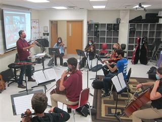 Director of Orchestras Mr. Patrick Rustandi (left) simultaneously conducts in-person and remote learners with the help of technology to create a better sense of unity among his musicians.