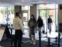 Students arrive on campus and proceed through a line of temperature checks and symptom screening.
