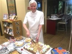 Sr. Barbara Thomas, ASCJ, cuts the first piece of cake at a BBQ held in her honor