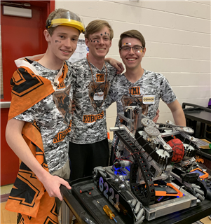 TMI Robotics team members Harrison Fentress, Josh Cross and John Fera get their robot ready for regional competition, March 2 in New Braunfels.