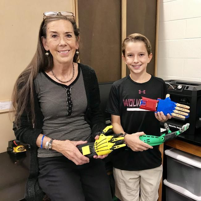 Anderson Carey and Dr. Holly Martin with 3D arms they have printed and built.