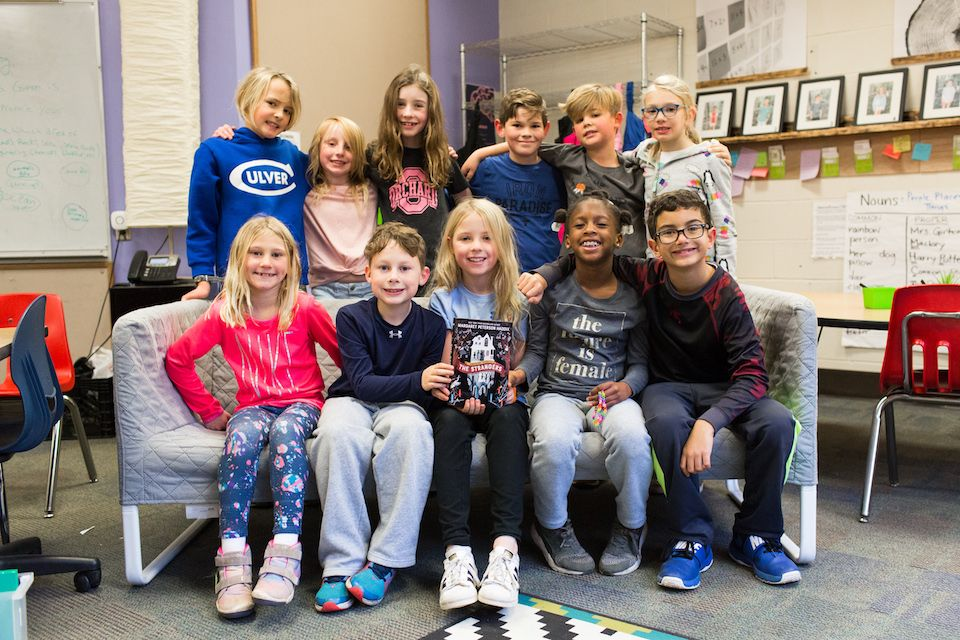 Some of Mrs. Girton's students pose with their favorite book, The Strangers by Margaret Peterson Haddix